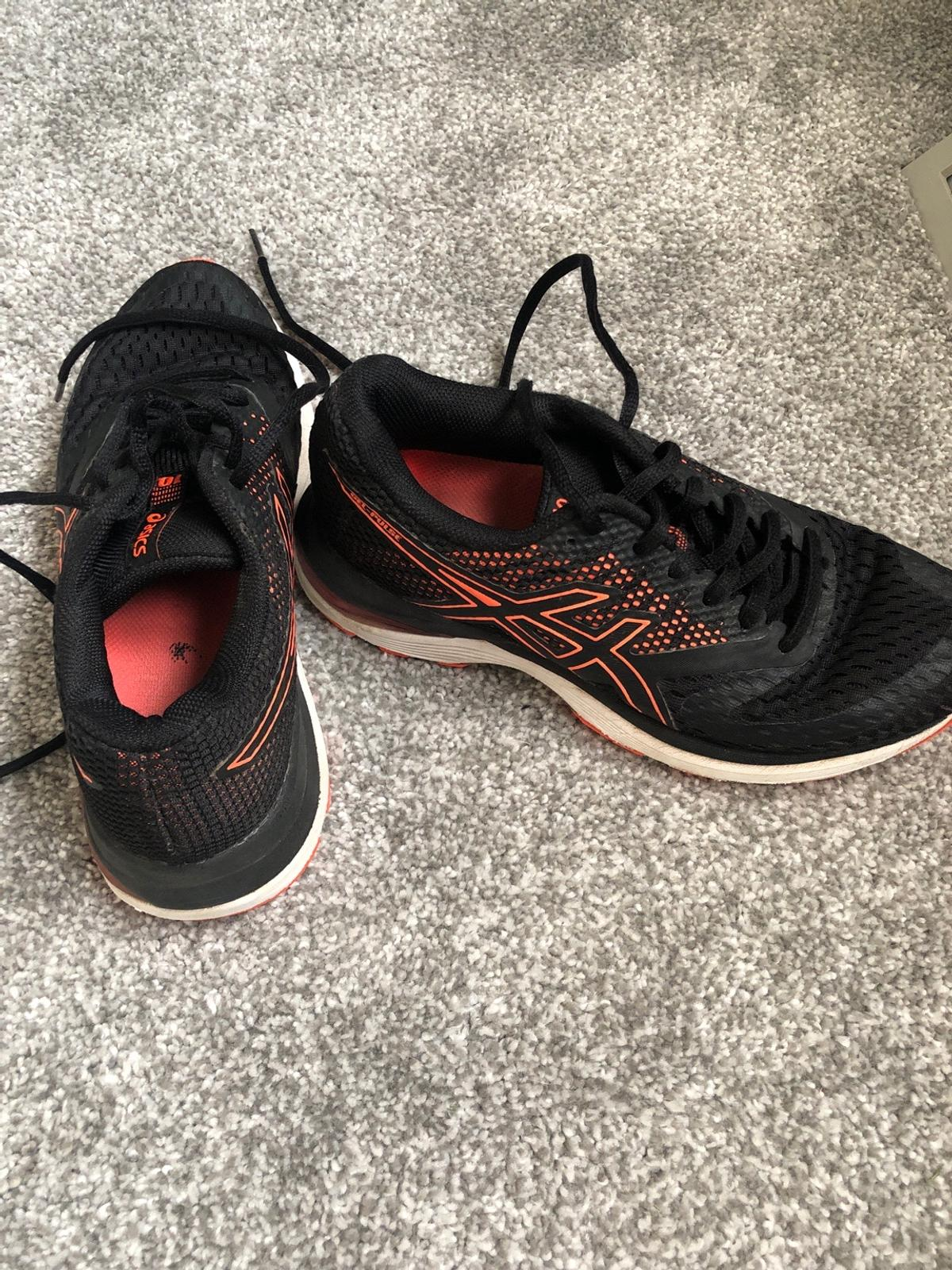 Black and orange netball / court shoe  Size 35.5 Europe / 5 US which is converted to a size three.  Worn but in fair condition.